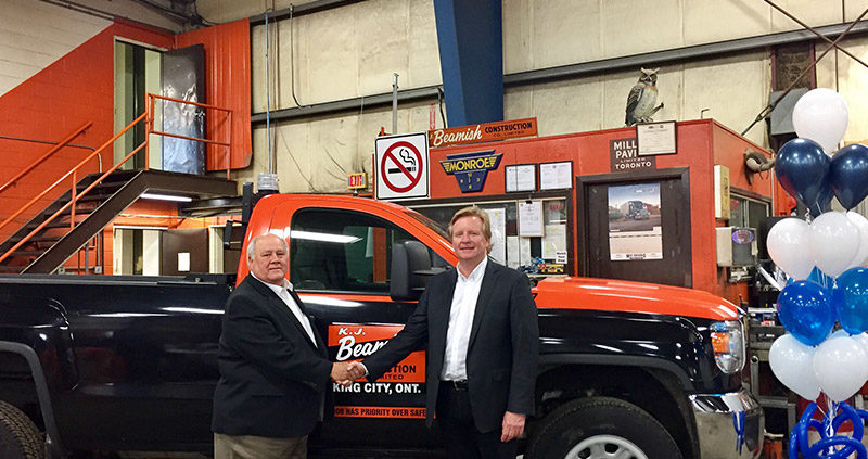 Shaking hands in from of an orange and back pick up truck